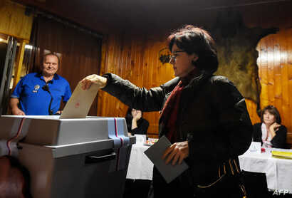 A woman casts her ballot during the first round of the presidential election at a polling station in Prague, Jan. 12, 2018.