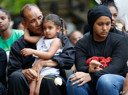 Mahmoud Hassanen Aboras father of Nabra Hassanen, who was killed over the weekend in a road rage incident, left, sits with family as he listens to speakers during a vigil in honor of Nabar Wednesday, June 21, 2017, in Reston, Virginia.