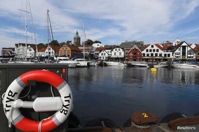 A lifebuoy is seen in front of boats in Stavanger harbour, Norway, Aug. 1, 2018.