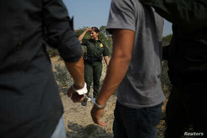 A U.S. border patrol agent stands next to men being detained after entering the United States by crossing the Rio Grande river from Mexico, in Roma, Texas, May 11, 2017.