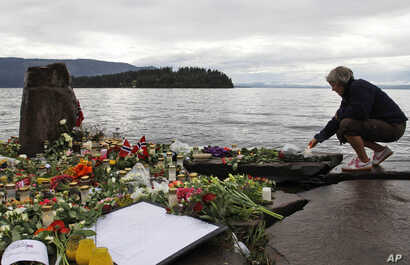 FILE - A woman lights a candle in Sundvollen, facing Utoya island, where gunman Anders Behring Breivik killed at least 68 people, near Oslo, Norway, July 26, 2011. Breivik told a court Wednesday he is the victim of inhuman prison conditions.