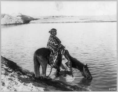 This circa 1913 photo shows a Navajo Indian seated on horse that is drinking from lake or river. The horse has always been considered sacred by the Navajo and figures prominently in songs and spiritual practices.