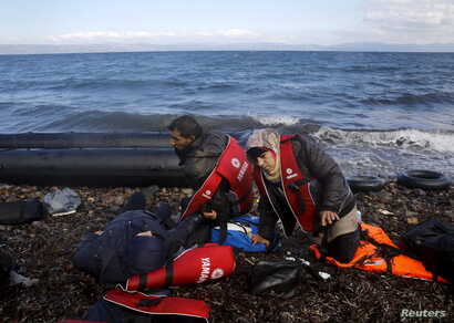 Syrian refugees lie exhausted moments after arriving by a raft at a beach on the Greek island of Lesbos, Oct. 25, 2015.