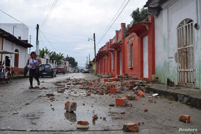 FILE - A woman walks past debris of a house damaged by an earthquake in Huixtla, in Chiapas state, Mexico, June 14, 2017.