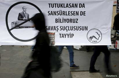 "A woman walks past a banner picturing Turkish President Recep Tayyip Erdogan that reads, ""When you arrest (journalists) or censor (media) we know that you are a war criminal, Tayyip,"" during a protest over the arrest of journalists Can Dundar and Erd..."