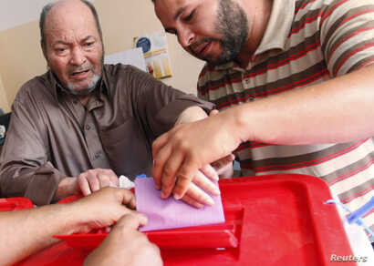 People help a voter place his ballot paper into the box at a polling station inside a school in Tripoli, June 25, 2014.