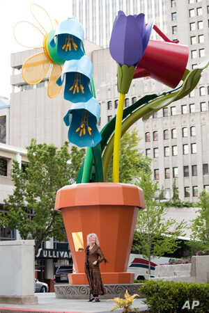 Artist Ginny Ruffner stands in front of her 28-foot [8.5 meter] aluminum-and-steel flowerpot. Seattle, Washington,  2011.