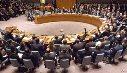 A gathering in the U.N. Security Council of foreign ministers lead by U.S. Secretary of State John Kerry vote on a draft resolution concerning Syria, at U.N. headquarters, Dec. 18, 2015.