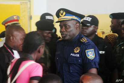 FILE - Former Kinshasa police chief, John Numbi, (C) walks into court on Jan. 27, 2011. Numbi was one of eight police officers accused of the death of human rights activist Floribert Chebeya in January 2010.