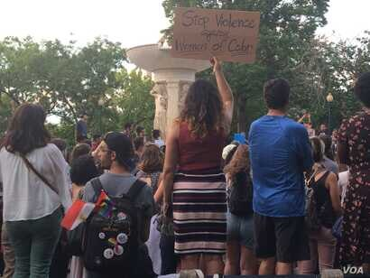 Attendees of a vigil honoring Nabra Hassanen carry signs calling for protection of women of color (E. Sarai/VOA)