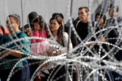 People line up to cross into the United States from Tijuana, Mexico, seen through barriers topped with concertina wire at the San Ysidro port of entry, Nov. 19, 2018, in San Diego.