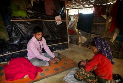 In this Jan. 14, 2018 photo, Rohingya Muslim refugee Mohammad Lalmia, 20, from the Myanmar village of Gu Dar Pyin, sits inside a makeshift shelter in Balukhali refugee camp, Bangladesh.