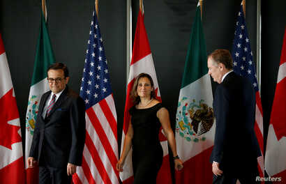 FILE - From left, Mexico's Economy Minister Ildefonso Guajardo, Canada's Foreign Minister Chrystia Freeland and U.S. Trade Representative Robert Lighthizer arrive for a meeting during the third round of NAFTA talks involving the United States, Mexico...