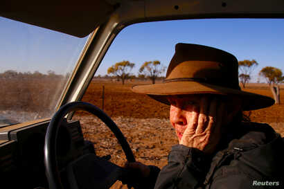Farmer May McKeown reacts as she drives her truck to feed the remaining cattle on her drought-affected property, located on the outskirts of the north-western New South Wales town of Walgett, in Australia, July 20, 2018.