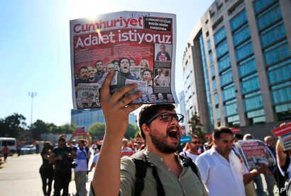 Activists, one holding a recent copy of the Cumhuriyet newspaper, march in Istanbul, July 24, 2017, protesting against a trial of journalists and staff from the newspaper, accused of aiding terror organizations. The newspaper headline reads in Turkis...