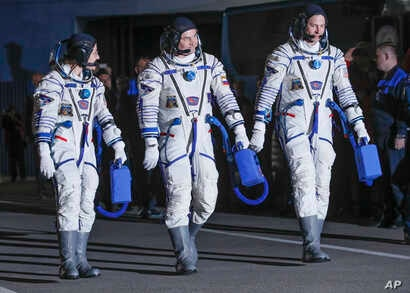 US astronauts Christina Hammock Koch (L), Nick Hague (R), and Russian cosmonaut Alexey Ovchinin, members of the main crew of the expedition to the International Space Station (ISS), walk before the launch of Soyuz MS-12 space ship at the Russian-leas...