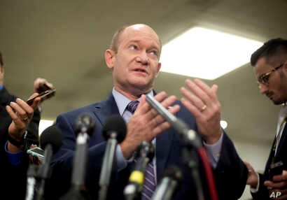 Sen. Chris Coons, a Delaware Democrat, gestures while speaking to reporters on Capitol Hill in Washington, Nov. 28, 2018.