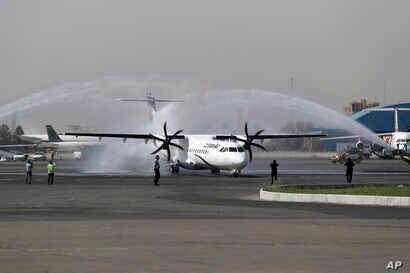 In this photo provided by Tasnim News Agency, a traditional water cannon salute welcomes an Iran Air's new commercial aircraft at Mehrabad airport in Tehran, Iran, Aug. 5, 2018.