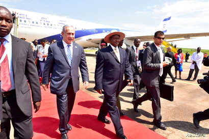 Israeli Prime Minister Benjamin Netanyahu (L) walks with Uganda's President Yoweri Museveni (R) after arriving to commemorate the 40th anniversary of Operation Entebbe at the Entebbe airport in Uganda, July 4, 2016. With them is Ugandan First Lady Ja...