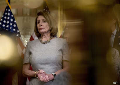 House Speaker Nancy Pelosi of California, accompanied by House Democratic members, listens to a reporter's question after signing a deal to reopen the government on Capitol Hill in Washington, Jan. 25, 2019.