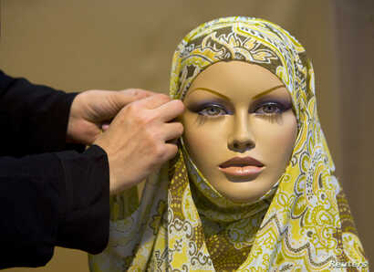 FILE - An Iranian designer sets-up a head scarf for a mannequin during an Islamic fashion exhibition at a cultural centre in Tehran. Jan. 15, 2008.