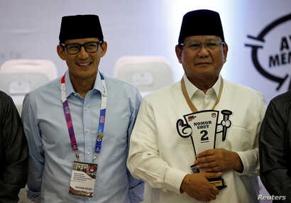 Presidential candidate in next year's election Prabowo Subianto, right, a retired special forces commander, and his running mate Sandiaga Uno attend a ceremony at the election commission headquarters in Jakarta, Indonesia, Sept. 21, 2018.