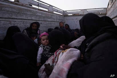 A baby is among men, women and children on a truck after being evacuated out of the last territory held by Islamic State militants, outside Baghuz, Syria, March 4, 2019.