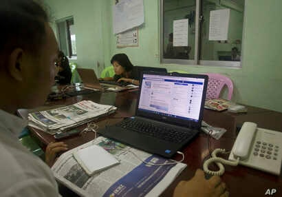 A reporter of The Voice Daily looks at its website as he and other reporters work in their newsroom in Yangon, Myanmar, June 5, 2017.