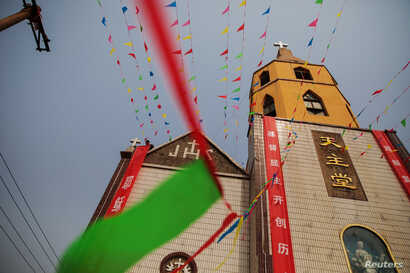 A man decorates a government-sanctioned Catholic church a day before Easter in Youtong village, Hebei province, China, March 31, 2018.