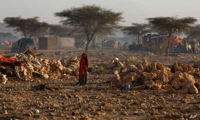 A Somali woman walks through a camp of people displaced from their homes elsewhere in the country by the drought, shortly after dawn in Qardho, Somalia, March 9, 2017.