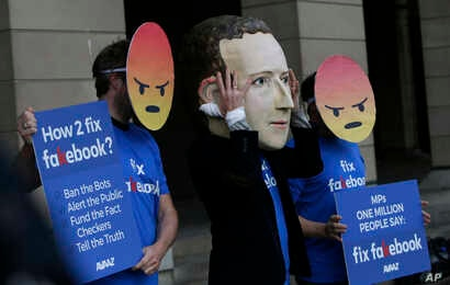 FILE - A protester wearing a mask with the face of Facebook founder Mark Zuckerberg, in between men wearing angry face emoji masks, is seen during a demonstration against Facebook outside Portcullis in London, April 26, 2018.