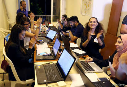 FILE - Beirut Madinati candidates and delegates cheer while monitoring ballot counts for the municipality elections after closing the polling stations during Beirut's municipal elections, Lebanon, May 8, 2016.