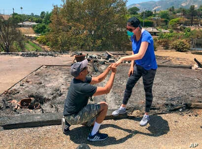 Resident Ishu Rao, on one knee, places this wife's wedding ring on her finger, next to the charred remains of their home in Goleta, Calif., July 8, 2018.  The California couple who lost their home in a wildfire made a new happy memory amid the ashes ...