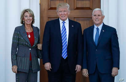 President-elect Donald Trump and Vice President-elect Mike Pence and Betsy DeVos pose for photographs at Trump National Golf Club Bedminster clubhouse in Bedminster, N.J., Saturday, Nov. 19, 2016.