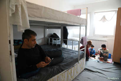 Marwan Ahman and his family rest in their room at the camp for refugees and migrants in the Belgrade suburb of Krnjaca, Serbia, Jan. 16, 2018.