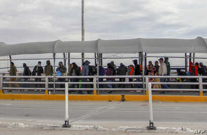 Migrants from Cuba, Venezuela and Central America queue at the Paso del Norte International Bridge in Ciudad Juarez, Chihuahua State, Mexico, to cross the border and request political asylum in the United States, on Jan. 9, 2019.