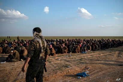 FILE - In this Feb. 22, 2019 file photo, U.S.-backed Syrian Democratic Forces fighters stand guard next to men waiting to be screened after being evacuated out of the last territory held by Islamic State group militants, near Baghuz, eastern Syria.