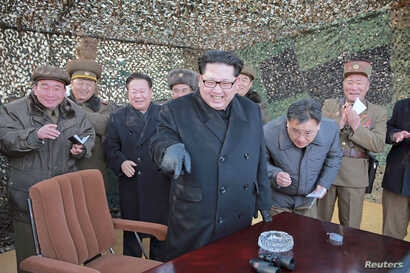 North Korean leader Kim Jong Un (C) smiles as he guides a test fire of a new multiple launch rocket system in this undated photo released by North Korea's Korean Central News Agency in Pyongyang, March 4, 2016.