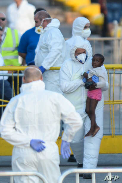 """A migrant child get assistance upon arriving aboard """"Lifeline"""", a vessel for the German charity Mission Lifeline, in the harbour of Valletta, Malta"""