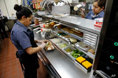Silvia Ruiz prepares a specialty sandwich at a McDonald's restaurant in Chicago, June 1, 2017. McDonald's is still trying to shake its image for serving junk food and has made a high-profile pledge to offer healthier options.