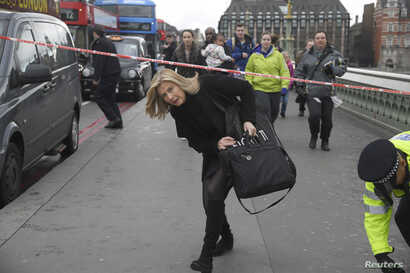 A woman ducks under a police tape after an incident on Westminster Bridge in London, March 22, 2017.