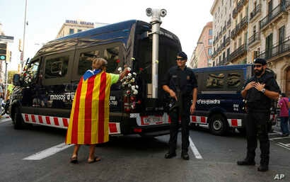 A woman with an ''estelada'' or Catalonia independence flag places a carnation on a vehicle belonging to police officers from Mossos d'Esquadra in Barcelona, Spain, Sept. 24, 2017.