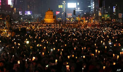 South Korean protesters hold candles during a rally calling for South Korean President Park Geun-hye to step down in Seoul, South Korea, Nov. 26, 2016. For the fifth-straight weekend, masses of protesters occupied major avenues in downtown Seoul dem...