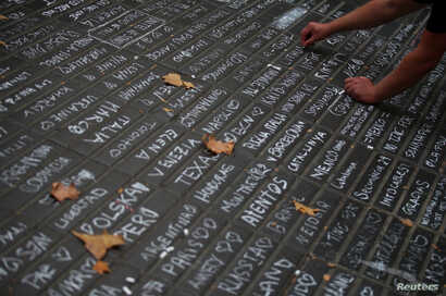 A person writes messages on a sidewalk at Las Ramblas in Barcelona, Spain, Aug. 19, 2017.