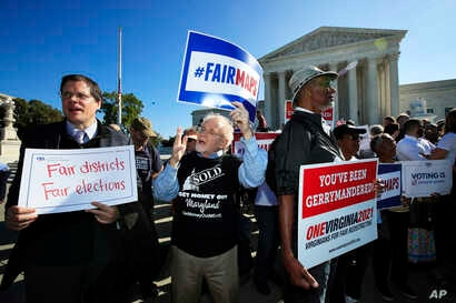 Protesters join others in a rally for fair elections, outside the U.S. Supreme Court in Washington, Oct. 3, 2017.