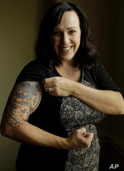 MJ Hegar pulls up her sleeve to reveal part of a tattoo that winds around her arm and back, for a portrait at her home in Round Rock, Texas, Aug. 9, 2018. Nine years after being shot down in Afghanistan, winning a lawsuit against the federal governme...