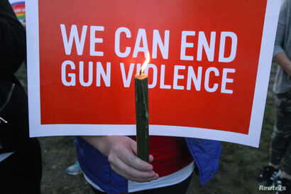 Mourners hold signs during a solidarity vigil in memory of victims of the Las Vegas music festival mass killing, in Newtown, Connecticut, site of the 2012 Sandy Hook school shooting, Oct. 4, 2017.