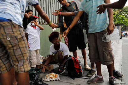 Youths eat a cake they'd found in a trash bag in Caracas, Venezuela, Feb. 27, 2019.