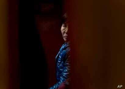A Chinese relative of passengers aboard a missing Malaysia Airlines plane looks out as she waiting for the latest news inside a hotel room for relatives or friends of passengers aboard the missing airplane in Beijing, China, March 11, 2014.