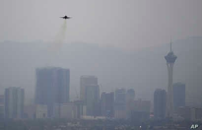 A fighter jet takes off from Nellis Air Force Base as a haze blankets the Las Vegas valley, July 31, 2018, in Las Vegas.